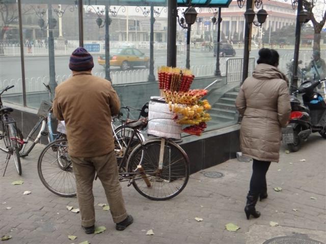 vendeur ambulant de brochettes de fruits caramélisés