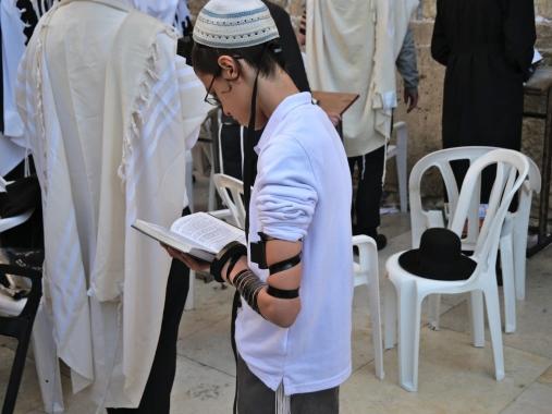 """Conformément aux instructions de la Torah, les Téfilines sont 2 boîtes contenant des passages de la Torah, une portée sur la tête, l'autre sur le bras gauche par des lanières. """"Vous reliez votre tête, votre cœur et votre main au moyen de ces lanières de c"""