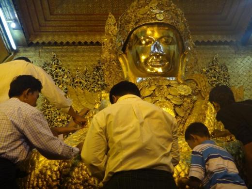 Des feuilles d'or sont collées sur la statue de Bouddha