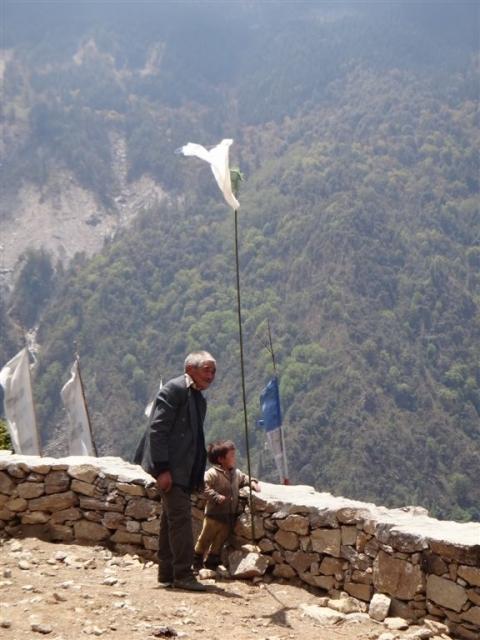 Le responsable de la Puja et son fils, devant le drapeau de prières installé pour l'occasion.