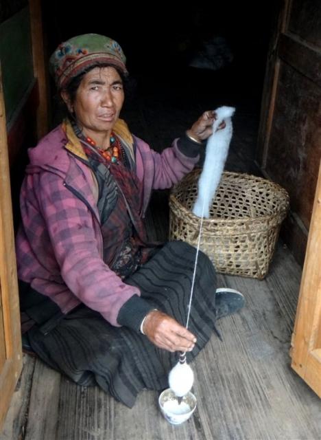 Notre hôte, le temps d'une averse, filant la laine.